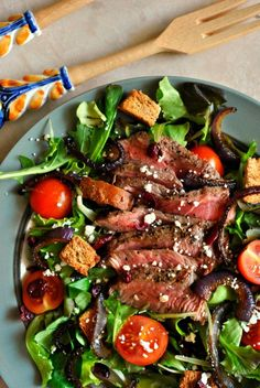 This Steak Salad with Caramelized Red Onions is full of amazing flavors! Feta, dried cranberries, cherry tomatoes and homemade croutons make this salad pop!