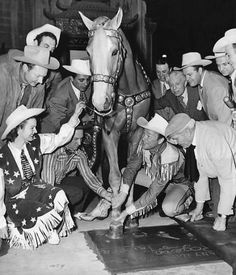 Roy Rogers becomes the first western star to be honored at Grauman's Chinese Theatre, along with his Palomino stallion, Trigger, whose hoof prints were also recorded for posterity. At left is Rogers' wife, Dale Evans, and showman Sid Grauman may be seen fourth from right in the background. April, 1949.