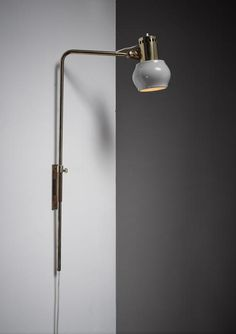 A rare Ilmari Tapiovaara 1960s table or wall lamp for Metallikolmikko Oy, Finland. The height-adjustable lamp is made of a brass stem and wall mount and an adjustable grey lacquered metal hood. There are some mild damages to the paint, but the lamp is in an overall good condition.