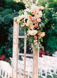 The romantic arrangement of flowers on this door adds rustic charm to this whimsical garden wedding.