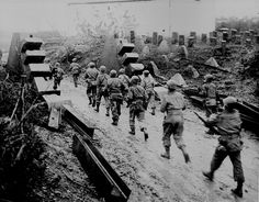 United States Army troops passing through dragon's teeth on the Siegfried Line in 1944.
