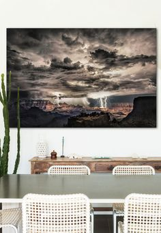 Lightning storm at night over the Grand Canyon photographed by Scott Stulberg. This dramatic piece of artwork is certainly an eye-catcher. With its dark skies and contrasting colors, this piece would look great in a neutral-colored and minimalist room.