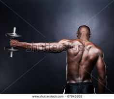 stock photo : Rear view of a young male bodybuilder doing heavy weight exercise with dumbbells against dark background