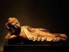 Bouddha Mandalay, 19ème siècle  Le Bouddha couché est un motif iconographique et statuaire important du Bouddhisme. Il représente le bouddha historique lors de sa dernière maladie, sur le point d'entrer dans le parinirvana. Allongé sur le flanc droit, il a la tête posée sur un coussin ou s'appuie sur son coude droit, soutenant sa tête de la main.