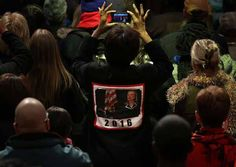 """WASHINGTON, DC - JANUARY 19: A woman wears a coat with a sign of """"Hillary Clinton for 2016"""" as she watches U.S. Vice President Joseph Biden participates during a Unite America in Service event on the National Day of Service as part of the 57th Presidential Inauguration January 19, 2013 at the DC Armory in Washington, DC. Vice President Biden and his family joined volunteers to pack care kits filled with necessities for deployed U.S. Service Members, Wounded Warriors, Veterans and First Responder Presidential Inauguration, Wounded Warrior, Vice President, Volunteers, Washington Dc, Warriors, Joseph, Presidents, January"""