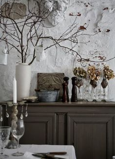 Sideboard in dark grey / taupe against a white wall.