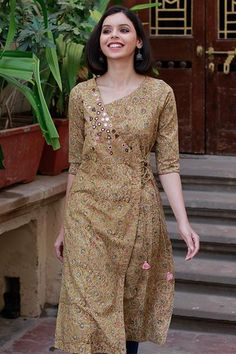 Muted hues of ochre and green in intricate Kalamkari motif block print on cotton, crafted into a calming and chic long kurta. With its stylish neckline, flattering sleeve length and tasselled doris, this design is inspired by the colours of the seaso Dress Neck Designs, Designs For Dresses, Blouse Designs, Kalamkari Kurta, Kalamkari Dresses, Simple Kurta Designs, Kurta Designs Women, Long Kurta Designs, Printed Kurti Designs