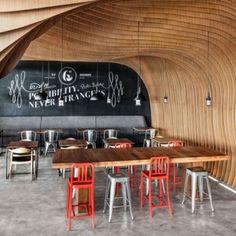 OOZN Design creates cavernous cafe  in Jakarta using undulating timber slats
