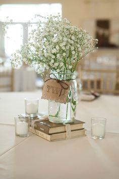 Centro de mesa con flores y libros.