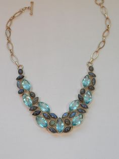 Nine gorgeous faceted Marquis-shaped London Blue Topaz gemstones are surrounded by 24 ocean green and blue-hued cabachon Marquis and Oval-shaped polished Labradorite gemstones, set in 925-hallmarked s