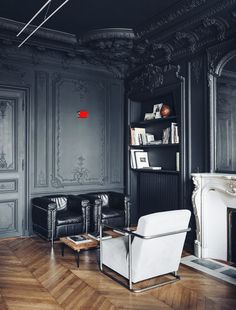 Dramatic black painted ceiling and wall mouldings with modern furniture and parquet herringbone floors.