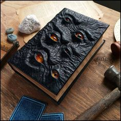Each one of these grimoire are one of a kind. Made using black bullfrog textured leather. Handmade glass eyes of various shapes and origins. Each page is stained using tea to to give an ancient fee...