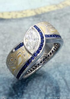 A truly unique engagement ring, this Mokume Wave Diamond Crossing Engagement Ring features a marquise cut moidssanite center stone, blue sapphire accents and our Summer Mokume Gane. Love this design? Make it your own by choosing your favorite metal, mokume and stones! #beautifulrings
