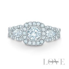 Beautifully framed pear-shaped diamond flank the center arrangement, while additional diamonds line the ring's shank.