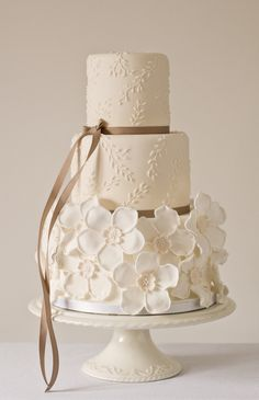 Ivory and taupe cake. White flowers and piping with delicate bow