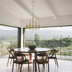 Designer Lori Yeomans selected a custom walnut table by Gianni Corvasce Restoration to accompany the vintage Kair Kristiansen dining chairs. A brass and Lucite chandelier add drama.