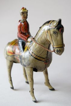 Antique Jockey on Horse Tin Litho Wind Up Toy  Early 20th Century, Marked Germany    Circa 1900-1920: Here is a fabulous five inch German tin wind up toy that comes complete with key and is in excellent working order and in fine condition. Great color on the early tin lithography and original harness. Marked underneath.