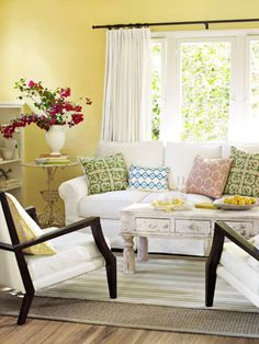 Light, Bright, and Fresh  Create a living room ripe with cheer and whimsy with a bright backdrop color, like the sunshiny hue shown here. Graphic pillows in magenta, emerald, and aquamarine positively pop. A slip-covered sofa, a weathered coffee table from H.D. Buttercup, and low-slung chairs by Four Hands serve to anchor the overall effect.
