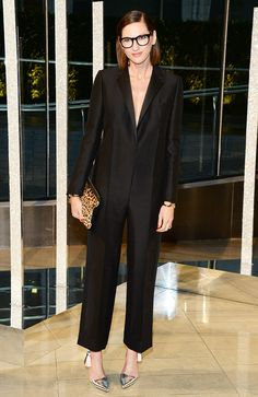 Jenna Lyons in her signature thick-frame glasses, a pantsuit meets jumpsuit, and silver tassel heels