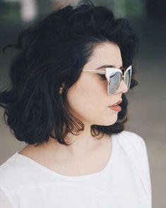 cute short haircuts, woman with short voluminous black wavy hair, wearing white top, and retro sunglasses with white frames