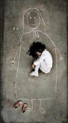 An orphan at the orphanage drew a mother on the floor, imagining she is sleeping in her mother's arms..