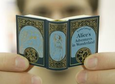 """A reader holds up Lewis Carroll's """"Alice's Adventures in  Wonderland"""" miniature book.  JOERG SARBACH / Associated Press"""
