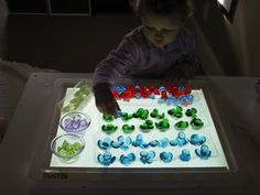 Amazing uses for the light table! Sorting colored marbles.