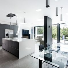 Open-plan kitchen with window wall, black feature pillar, black cabinetry and neutral gloss island unit