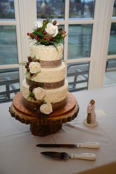 A rough textured wedding cake accented with burlap ribbon and fresh flowers.