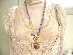 Eclectic necklace featuring a yummy vintage floral micro mosaic pin (back removed) , a vintage California bar finding , vintage blue glass beads culled from broken jewelry , enamel number tag , vintage recycled cameo links , a recycled butterfly link , a vintage pansy pin (back removed) and recycled vintage metal filigree bead chain which features its original box clasp.  approx. 26 1/4 approx. 45mm round on the pendant  ref- California dreamin