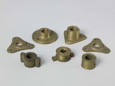 Anonymous | Zeven metalen bossen voor blokschijven, Anonymous, 1850 - 1865 | Zeven verschillende messing bossen voor blokschijven. Drie zijn driehoekig; een is groot en rond; een kleine ronde met twee nokken heeft een klinkring erop geklonken; een andere kleine ronde heeft twee nokken met gaten voor nagels; de laatse is gewoon rond met twee spijkergaten.