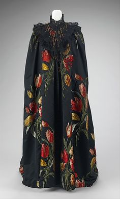 Haute Couture Charles Frederick Worth evening cape  gown from 1889. Silk textile Tulipes Hollandaises designed to showcase its to the extreme and has a repeat which is over three feet long making it stunning but also making it extremely difficult to weave. The dramatic fabric, was exhibited at the Exposition Universelle of 1889 in Paris and won a grand prize. A brilliant seductive femme fatale for 1880s and 1890s, tulip flower in vibrant colors against the deep black background. #Haute…