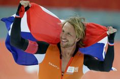 Michel Mulder from the Netherlands holds his national flag and celebrates winning gold in the men's 500-meter speedskating race at the Adler... His identical twin brother took the bronze.