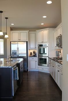 I like this kitchen layout with wall ovens on the corner. White cabinetry and wide plank dark wood floors Off White Kitchen Cabinets, Off White Kitchens, Cream Cabinets, Elegant Kitchens, Kitchen Redo, Beautiful Kitchens, New Kitchen, Home Kitchens, White Cabinets