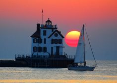 Lorain lighthouse and sailboat at sunset - Lake Erie