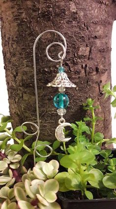 Miniature Fairy garden lantern, wind-chime. Aqua blue glass bead with moon charm. Lantern length is approx. 2 Comes with shepherds hook approx. 8 **If you would prefer a Plain Shepherds Hook, Just let me know at checkout. Made for indoor or outdoor use, but metal may tarnish outside. Please contact me with any questions. Sorry, No international shipping at this time.