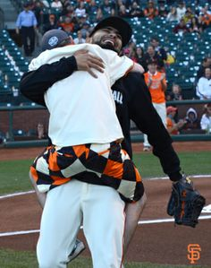 Sergio Romo receives a bear hug after catching the Ceremonial First Pitch on Autism Awareness Night.