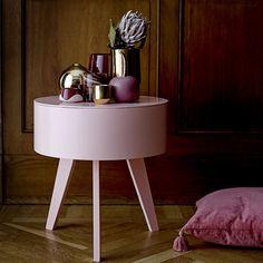 Une table d'appoint rosée avec 3 pied et des bougies bordeaux et dorées