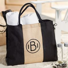 "Our largest jute tote has colorblocked black and natural jute panels with black embroidered initial. Cotton web handles and side rope ties for adjustable size. Laminated wipe-clean interior and interior pocket. 19"" x 22"" x 8""."