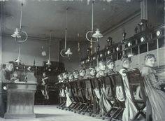 Fotografi av kvinner som sitter på rad langs telegrafapparater, med ryggen mot fotografen, men tittende over skuldra.
