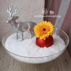 Coupe en verre avec de la neige florale décorée d'un mignon petit élan argenté et un germini jaune dans une boule rouge pailletée.