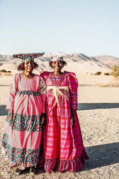 'Namibia Herero Women' Photographic Print by Kara Rosenlund. These brightly coloured women belong to the Herero Tribe of Namibia. Walking across the horizon after a long day with their cattle, their vibrant traditional clothes pop out of the desert sandy haze. © Kara Rosenlund  Shop here: http://shop.kararosenlund.com/namibia-herero-women-photographic-print/
