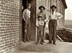 Payne Mill: January 1909. Macon, Georgia. This boy has worked in Payne Cotton Mill for 2 yrs. Runs four sides and earns 52 cents a day. Overseer has hand on boys shoulder. He said this mill made 70% profit last year and expects to make 100% this year. Owned by Bibb Mfg. Co. Photo by Lewis Wickes Hine.