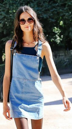 A classic overall dress over a blue crop top