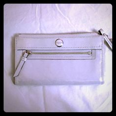 """COACH POPPY METALLIC LEATHER ZIPPY (white suede) Brilliantly foiled metallic leather gives this versatile, hand-assembled wallet a subtle sparkle and a velvety soft texture, while a brightly striped interior keeps everything organized. Metallic leather credit card and multifunction pockets. Zip-top closure, fabric lining. Strap with clip to form a wrist strap or attach to the inside of a bag. Outside open and zip pockets. 7 3/4"""" (L) x 4 1/4"""" (H). In Like-New condition, used only twice…"""