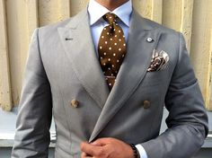 Light grey double-breasted jacket, white shirt, brown tie with white polka dots