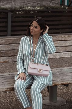 Stella Asteria wearing striped suit and pink Chanel chevron bag