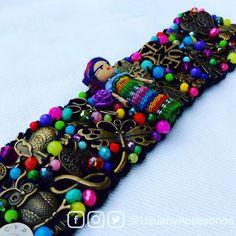 Brazalete tejido con muñequita quita penas, bordado con dijes y pedrería de colores.  Www.facebook.com/uzuanyaccesorios