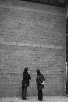 """Santiago Sierra """"Palabra Tapada"""" el artista tapa con plástico negro la palabra España del pabellón nacional en la 50ma Bienal de Venecia (2003). Asi mismo construye un muro de ladrillo visto bloqueando la entrada principal, restringiendo el acceso al público quien debía ser exclusivamente español y entrar desde la parte trasera, previa presentación de su Documento Nacional de Identidad o Pasaporte en vigor."""