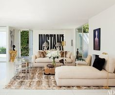 In architect and designer Daniel Romualdez's Los Angeles living room, a Romualdez-designed sofa and daybed, both upholstered in a raw silk, are grouped with vintage acrylic armchairs by Paul Rudolph | archdigest.com